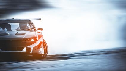 Dryfowanie samochodu, rozmazany samochód wyścigowy z rozmyciem obrazu z dużą ilością dymu z płonących opon na torze prędkości