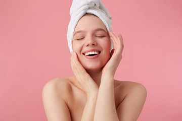 Portrait of young happy woman after shower with a towel on her head, broadly smiles with closed eyes, touches face and smooth skin, stands over pink background.