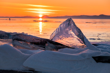Transparent ice on Lake Baikal at sunset.