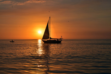 sunset as sail boat sails in front of sun