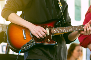 Close-up of the hands of a rock or jazz musician playing an electric guitar during an open-air concert on stage. The guy performs with a music band. Energy, drive and creativity.