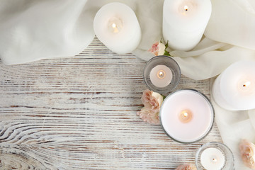 Flat lay composition with burning aromatic candles and roses on wooden table. Space for text