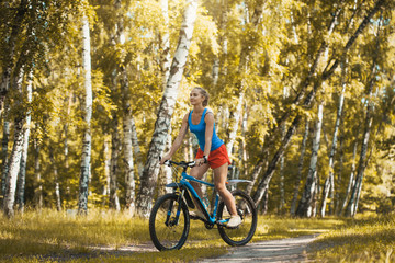 cute blonde woman cyclist cycling mountain bike on the birch forest trail
