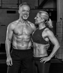 Sportliches Paar mittleren Alters hat zusammen Spaß beim Sport. Die sportliche blonde Frau in den Vierzigern und der athletische Mann in den Fünfzigern beim Krafttraining. Arm in Arm.