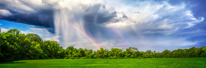 Rain And Rainbow Over Rural Landscape With Trees And Plant Crop