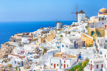 Travel Destinations. Picturesque Cityscape of Oia Village in Santorini Island Located on Volcanic Calderra at Daytime. Traditional Windmills on Background.