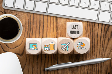 Last minute online travel specials concept with a row of wooden blocks with icons depicting laptop, luggage, airplane and beach alongside a computer with mug of coffee