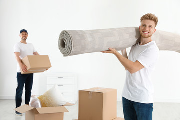 Moving service employees with cardboard boxes and carpet in room