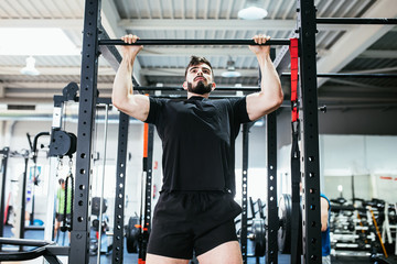 man doing pull-ups exercises in the gym