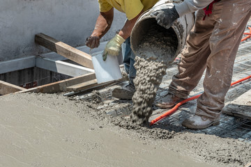 Pouring concrete at a construction site. Filling a rooftop with cement over the pipelines