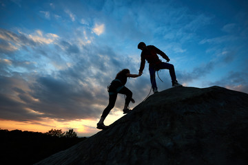 Silhouettes of two climbers reaching summit, one holding hand of partner assisting to make last step to top. Young man and woman athletes bouldering on high rock. Amazing sky and sunset on background.