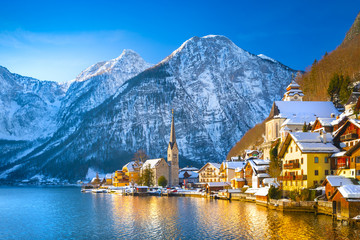 Classic postcard view of famous Hallstatt lakeside town in the Alps with traditional passenger ship on a beautiful cold sunny day with blue sky and clouds in winter, Austria