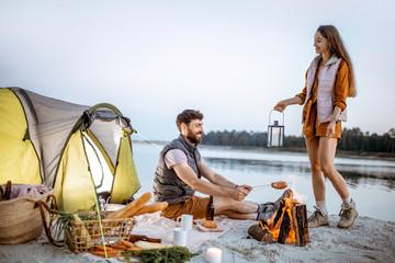 Młoda para zabawy na kempingu na plaży przy kominku wieczorem