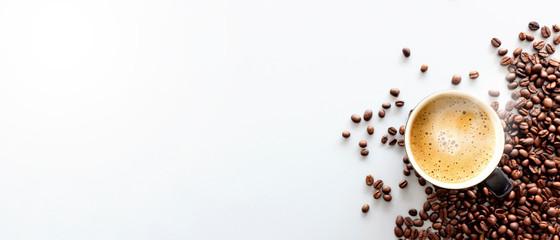 gorące espresso i ziarna kawy na białym stole z delikatnym ustawieniem ostrości i światłem w tle. widok z góry