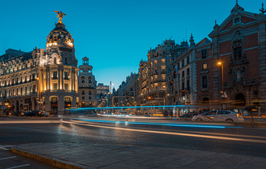 Lighttrails and Traffic on the crossing Alcala and Gran Via street in Madrid by twilight.The Gran Via is unofficially considered main street of Spain capital.