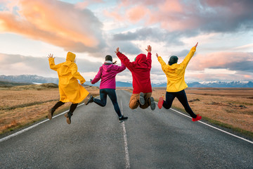 four friend jump on the road at sunset