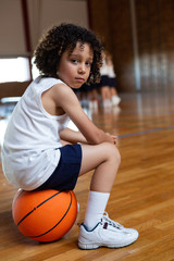Schoolboy sitting on basketball and looking at camera