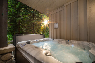 A outdoor hot tub near a forest with a sunburst coming through the trees.