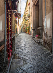 Charming, empty, narrow, cobbled street lined with old, stone buildings in Italy