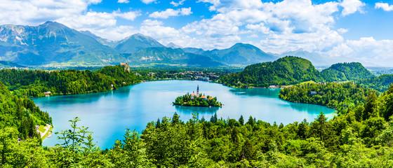 Piękny krajobraz jeziora Bled wyspa kościelna pośrodku i zamek w tle białego zachmurzonego nieba z punktu widzenia Ojstrica w Bled, Słowenia