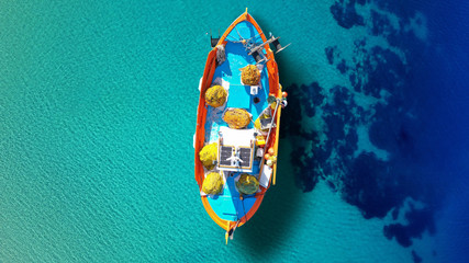 Aerial top view photo of traditonal fishing boat docked in turquoise crystal clear Ionian island sea, Greece