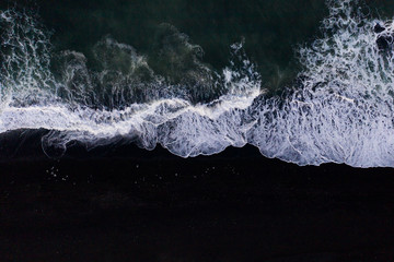 Top down view of scenic sea waves on black sand beach in Iceland