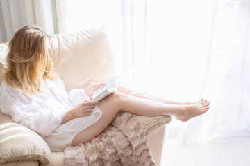 Woman sitting in white armchair and reading the book  at the morning in bedroom. Relaxing and good morning concept.