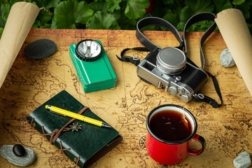 Vacation trip with a map next to a cup of tea and travel equipment, retro style