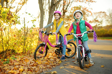 Cute little sisters riding bikes in a city park on sunny autumn day. Active family leisure with kids.