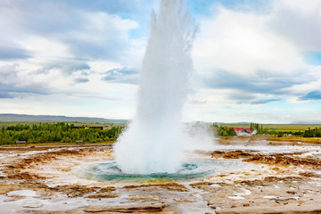 Iceland, Golden Circle touristic itinerary - iconic landmark Strokkur Geysir. Eruption of Strokkur geyser in Iceland.  Natural wonder - hot sprint that erupting every 5 minutes. Geothermal fields.