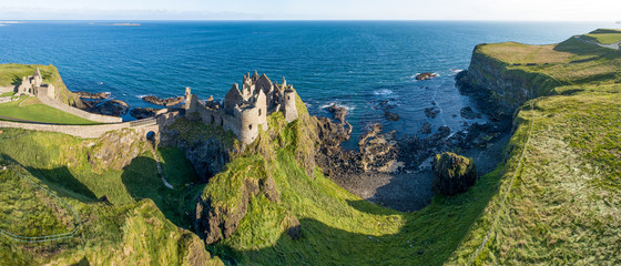 Ruins of medieval Dunluce Castle on a steep cliff. Northern coast of County Antrim, Northern Ireland, UK. Aerial wide panorama in sunrise light