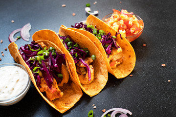 Traditional Mexican tacos with chicken, grilled vegetables, onions and purple cabbage, served with white and red sauce and onion rings. Close-up. Dark background. Copy space