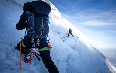 Two mountaineers climb steep glacier ice crevasse extreme sports, Mont Blanc du Tacul mountain, Chamonix France travel, Europe tourism.