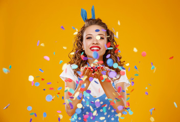 cheerful funny young woman with festive confetti on yellow .