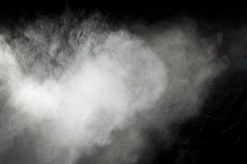 White powder explosion on black background. Abstract white dust texture fly on the air.