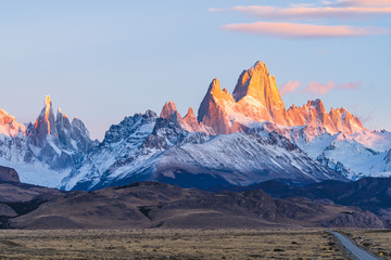 Beautiful dawn golden orange light of sun rise over the Fitz Roy and Cerro Torre peak snow mountain in the morning beside the route 40 road from El Calafate to El Chalten, south Patagonia, Argentina