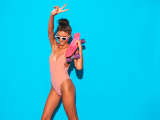 Young beautiful sexy smiling hipster woman in sunglasses.Trendy girl in summer swimwear bathing suit. Positive female going crazy with pink penny skateboard,isolated on blue.