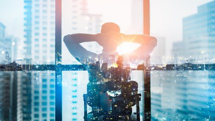 Portrait of relaxed businessman in modern office.Double exposure city of Business young man relax after work of office window with business district view.
