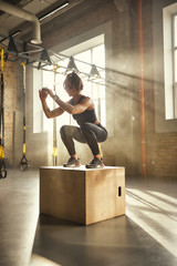 Challenging myself. Side view of athletic woman in sportswear doing squat while standing on wooden box at gym