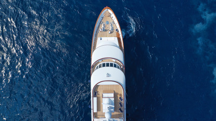 Aerial drone photo of luxury yacht with wooden deck in deep blue sea of iconic island of Mykonos near super Paradise beach, Cyclades, Greece