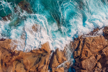 Coast of desert island with blue turquoise water beats on rocky reef. Aerial top view.