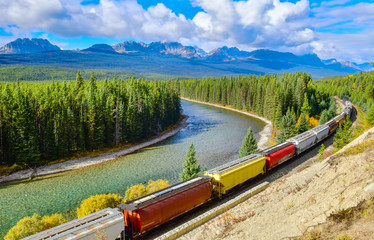 Long freight comtainer train moving along Bow river in Canadian Rockies ,Banff National Park, Canadian Rockies,Canada