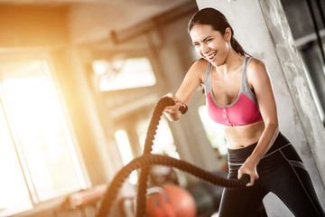 Young healthy woman exercising with battle rope at the gym