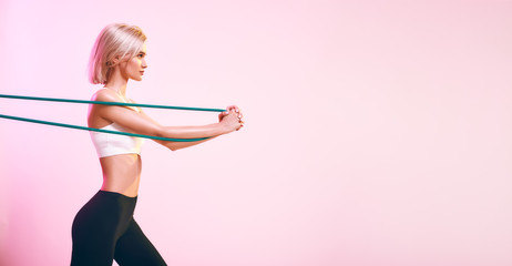Active lifestyle. Sporty beautiful woman in white top and black leggings exercising with resistance band while standing against pink background in studio