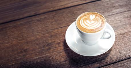 Zamyka w górę gorącej cappuccino białej filiżanki z kierową kształta latte sztuką na ciemnego brązu starego drewna stole przy kawiarni, jedzenia i napoju pojęciem ,.
