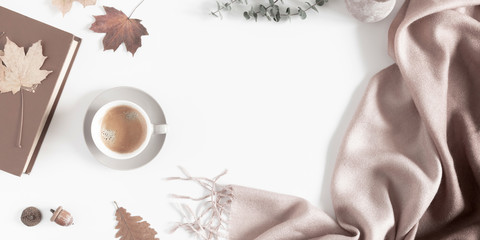 Autumn home cozy composition. Dried autumn leaves, cup of coffee, book, scarf, flowers on white background. Fall background. Flat lay, top view, copy space