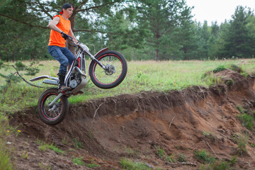 Motorcycle rider Caucasian man jumping in sandy pit with his trial bike, copy space