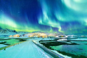 Niesamowity widok na cuda przyrody Northern Lights lub Aurora Borealis nad oświetleniem mostu Kubholmenleia przechodzącego przez fiord. Archipelag Lofotów w Norwegii, położenie nad kołem polarnym.