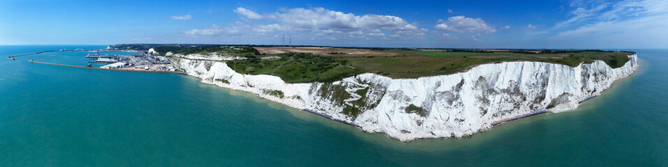 Aerial panorama of Port of Dover with ferry ships docked in passengers terminal and view over white cliffs, coastal countryside on a sunny summer day, south east England .