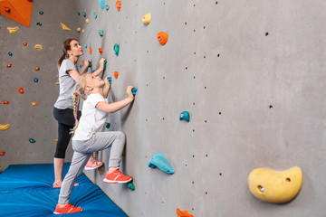 Young woman with her little daughter climbing wall in gym